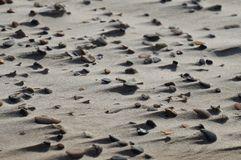 Wind-swept rocks on fine sand depicting the force of wind. Wind-swept rocks with small dunes accumulating behind them. The power and dynamics of the wind and Stock Photo
