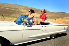 Wind in their hair. Wind in the hair of party girls speeding in a convertible with the top down out on a  country road. Shallow depth of field Royalty Free Stock Photos