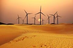 Windmills generating alternative green energy in the sand dessert. Wind tourbines generating alternative green energy in the sand dessert at sunset royalty free stock photo