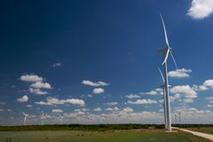 Wind trubines. In a field with blue sky and white clouds Stock Photo