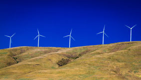 Wind tubines in front of a clear sky. A deep blue sky and grassy hillside frame a series of  wind turbines Stock Photos