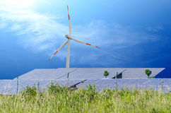 Wind turbin and solar panels. Solar cells on green field on blue sky with sun rays Stock Images