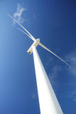Wind turbine. Generator view with blades spinning around under a beautiful blue cloudy sky Royalty Free Stock Photos