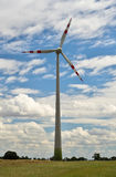 Wind turbine. Against a cloudy sky. Motion blur is used to show the movement of the turbine Royalty Free Stock Images