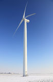 Wind turbine. In a field covered by sbow in winter.There is a little motion blur at the tips of the blades Royalty Free Stock Photos