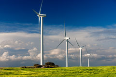 Wind turbine. White wind turbine generating electricity on cloudy sky Stock Images