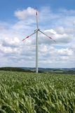 Wind turbine. A lone wind turbine in a corn field, against a sky of dramatic clouds Stock Photos