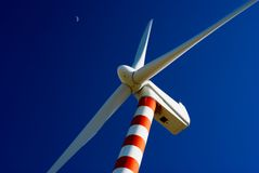 Wind turbine. With deep blue sky and moon stock photography