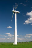 Wind Turbine. One wind turbine against blue sky with white clouds royalty free stock image