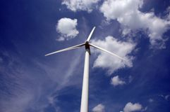 Wind turbine. On blue and cloudy sky background stock image