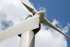 Wind turbine. Against a cloudy blue sky stock images