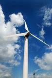 Wind turbine. Against a cloudy blue sky royalty free stock photography