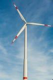 Wind turbine against a blue hazy sky Royalty Free Stock Photo
