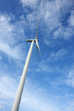 Wind turbine against blue sky. Wind power generated by a huge turbine with nice contrast against the blue sky Stock Photo