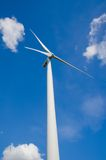 Wind turbine against cloudy blue sky Royalty Free Stock Images