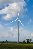 Wind turbine against cloudy blue sky Stock Photography
