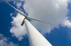 Wind turbine against cloudy blue sky Royalty Free Stock Photos