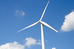Wind turbine against cloudy blue sky Stock Image