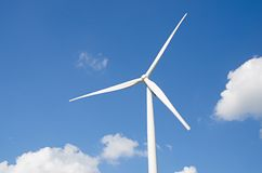 Wind turbine against cloudy blue sky Royalty Free Stock Photo