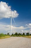 Wind turbine against cloudy blue sky Royalty Free Stock Image