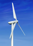Wind turbine against cloudy blue sky Stock Photo