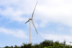 Wind turbine against mountain in the forest area Stock Photos