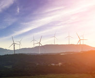 Wind turbine against mountain in the forest area. Wind turbine against mountain under the blue sky Stock Photography