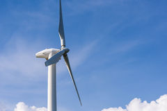 wind turbine against partly cloudy blue sky Royalty Free Stock Photography