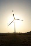 Wind turbine against sun Stock Images