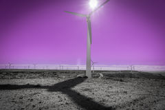 Wind turbine against sun, windmill farm and pink sky Stock Images