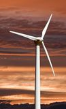 Wind turbine against a sunset sky. A wind turbine used for electricity generation against a sunset sky Royalty Free Stock Photography