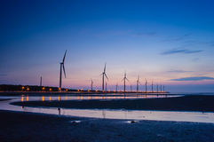 Wind turbine. Array at seashore wetland by the sunset stock photography