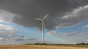 Wind turbine in the background of a dark cloud. Wind turbine against the background of the evening sky. Alternative energy ecological problems wind turbines in stock footage