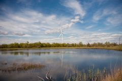Wind turbine on the background of the lake Stock Photos