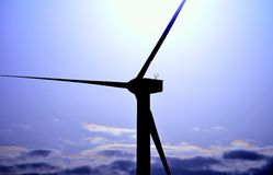 Wind turbine backlit with color effects at sunrise Royalty Free Stock Images