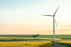 Wind turbine and beautiful fields at sunset. Space for text stock photo
