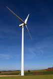 Wind turbine on blue sky Royalty Free Stock Images
