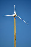Wind turbine and blue sky. Wind turbine for sustainable energy production. Single windmill and blue sky Stock Images