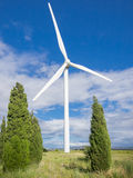 Wind turbine on blue sky with clouds Stock Photos
