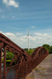 Wind turbine and blue sky. Old rusty bridge and wind turbine in bright,sunny day near Killorglin,Kerry,Ireland Royalty Free Stock Photo