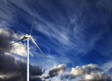Wind turbine and blue sky with storm clouds Royalty Free Stock Image