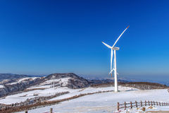 Wind turbine and blue sky in winter. Royalty Free Stock Image