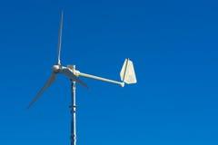 Wind turbine on a brilliant blue sky. A wind turbine against a bright blue sky royalty free stock photo