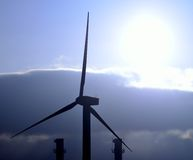 Wind turbine and chimneys with intense morning sun Stock Photo