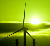 Wind turbine and chimneys of power plant at sunrise Stock Image