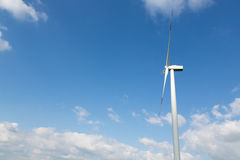 Wind turbine for clean energy production in front of blue sky Stock Photo