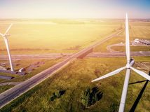 Wind turbine close-up with powerful turbines on background of clear bright blue sky and summer green grass stock photos