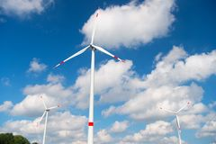 Wind turbine on cloudy blue sky. Alternative energy and electricity source. Global warming. climate change and ecology. Eco power. And green technology concept Stock Image