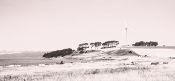 Wind turbine on coastline. Black and white lithographic view of wind turbine on hillside by sea stock image