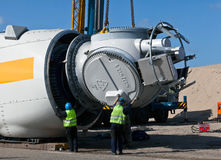 Wind turbine construction site. At a wind turbine construction site workers are mounting the rotor hub onto the turbine gearbox or generator. Part of the on the Stock Images